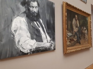 Pei-Ming next to Courbet's painting of Proudhon